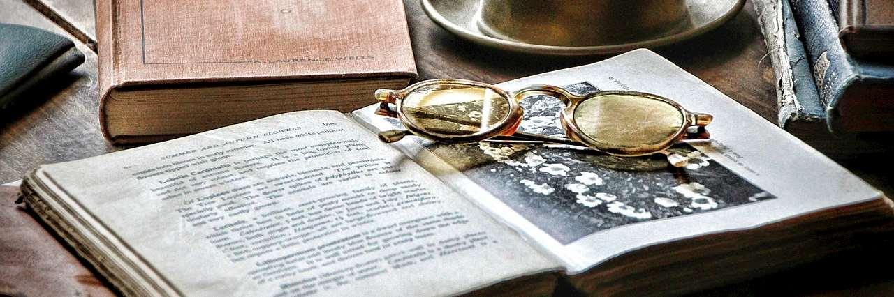 Gammal uppslagen bok med läsglasögon på